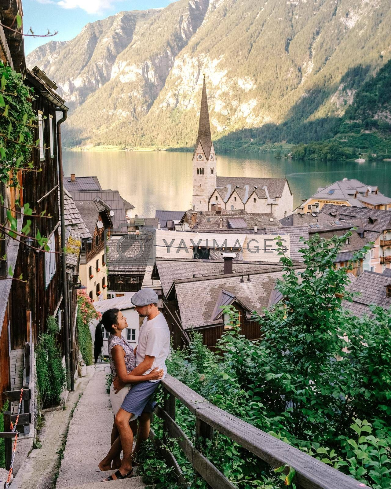 couple visit Hallstadt town, View of Hallstatt Hallstadt town with reflection in lake with blue sky above