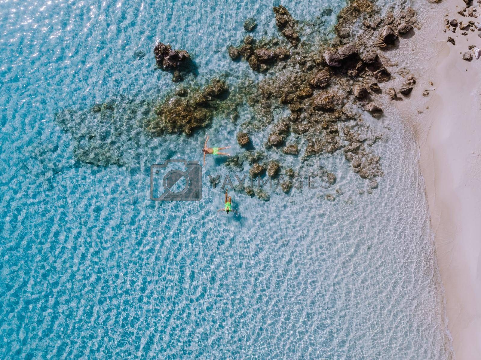 Tropical beach of Voulisma beach, Istron, Crete, Greece ,Most beautiful beaches of Crete island -Istron bay near Agios Nikolaos drone aerial view, woman in swimsuit on the beach, couple on vacation Greece snorkeling in the ocean