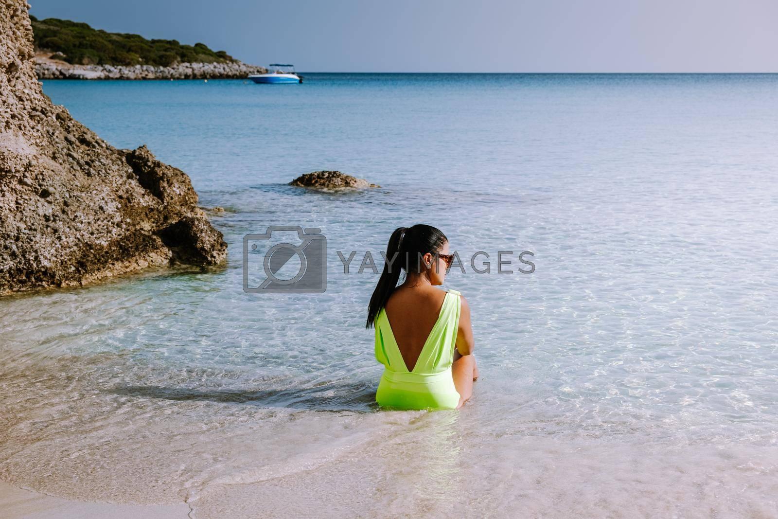 Tropical beach of Voulisma beach, Istron, Crete, Greece ,Most beautiful beaches of Crete island -Istron bay near Agios Nikolaos. young woman on the beach of Crete