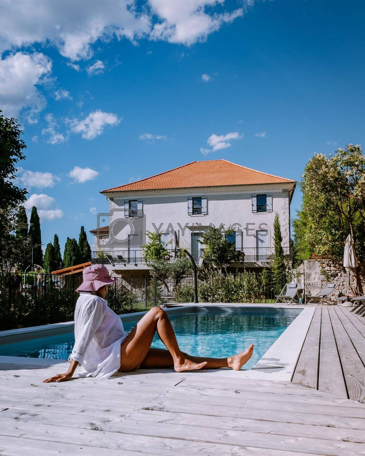 French vacation home with wooden deck and swimming pool in the Ardeche France Europe. woman relaxing by the pool with wooden deck during luxury vacation at an holiday home in South of France