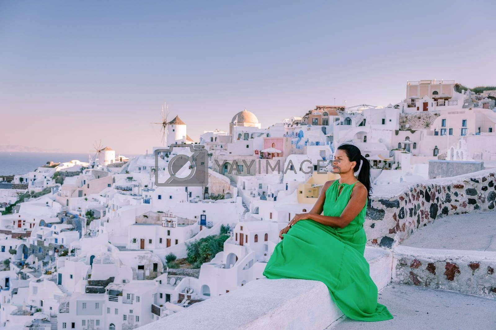 Sunset at the Island Of Santorini Greece, beautiful whitewashed village Oia with church and windmill during sunset, streets of Oia Santorini during summer vacation at the Greek Island Woman on luxury vacation Greece