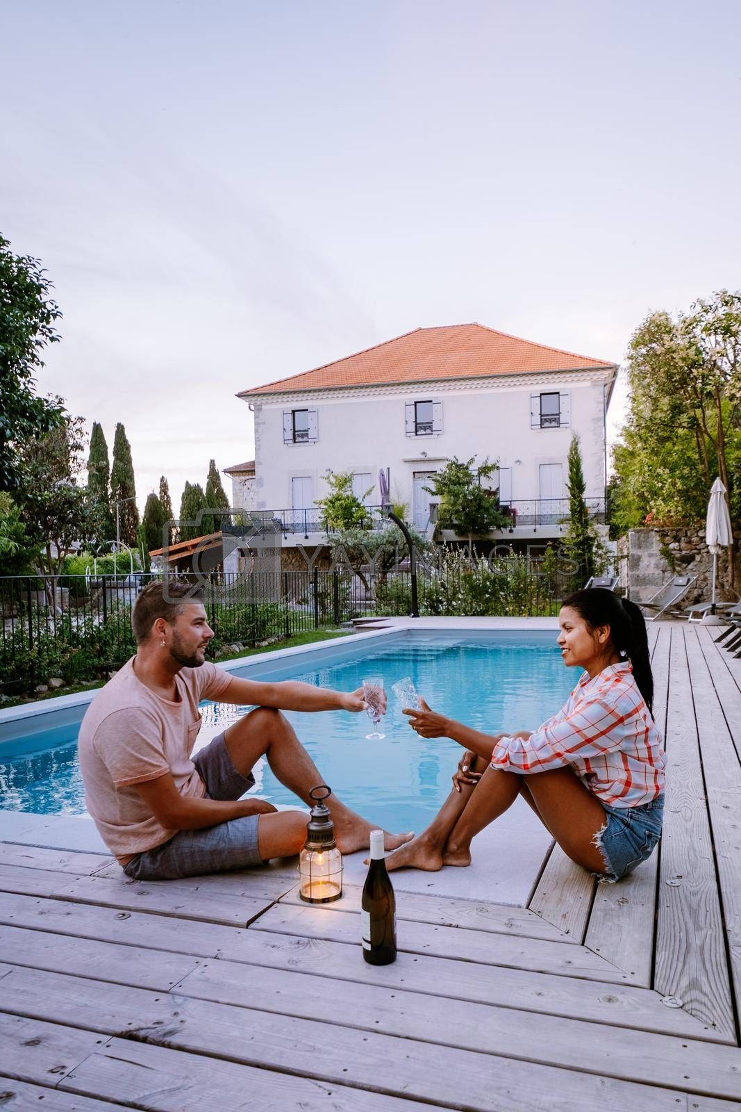 French vacation home with wooden deck and swimming pool in the Ardeche France Europe. Couple relaxing by the pool with wooden deck during luxury vacation at an holiday home in South of France