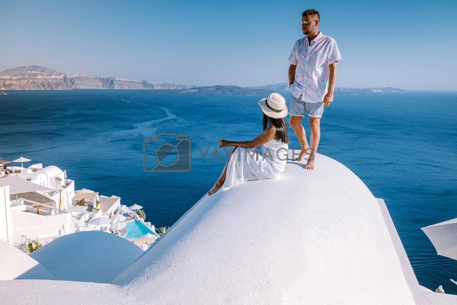 Royalty free image of couple men and woman on vacation Santorini, View to the sea and Volcano from Fira the capital of Santorini island in Greece by fokkebok