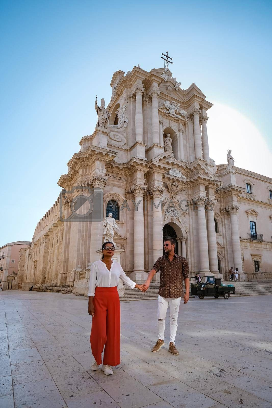 Royalty free image of couple men and woman on citytrip Ortigia in Syracuse in the Morning. Travel Photography from Syracuse, Italy on the island of Sicily. Cathedral Plaza and market with people whear face protection during the 2020 pandemic by fokkebok
