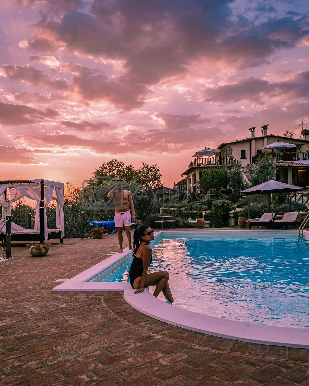 Royalty free image of Luxury country house with swimming pool in Italy, Couple on Vacation at luxury villa in Italy, men and woman watching sunset by fokkebok