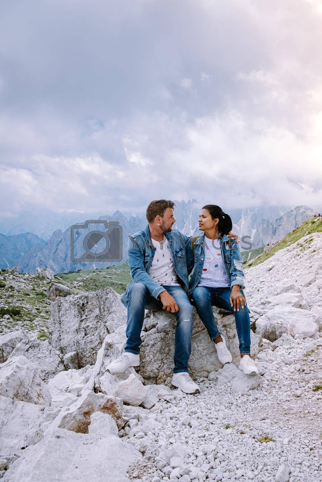 couple hiking in the italian dolomites during foggy weather with clouds, Stunning view to Tre Cime peaks in Dolomites, Italy. Europe