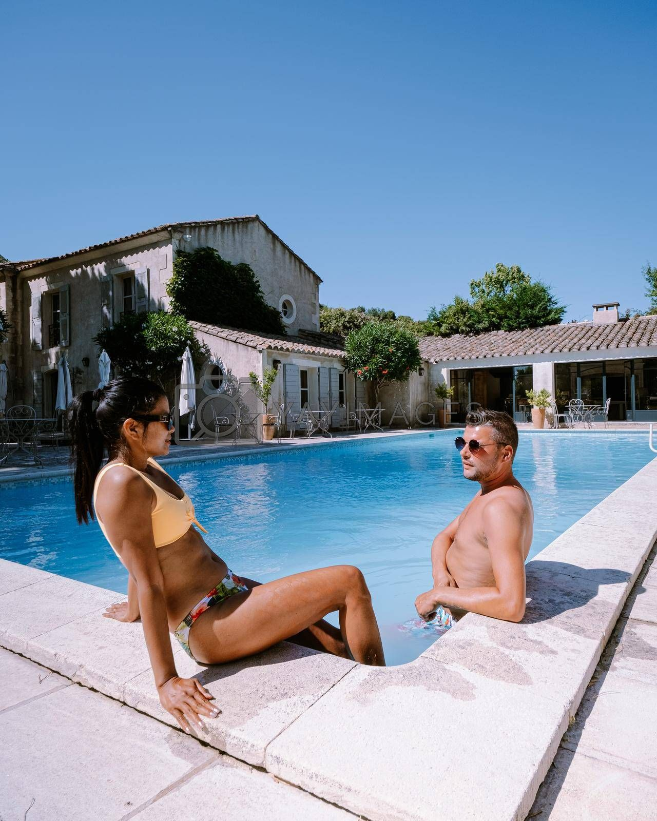 Royalty free image of couple relaxing by the pool in the Provence France, men and woman relaxing by pool at luxury resort by fokkebok