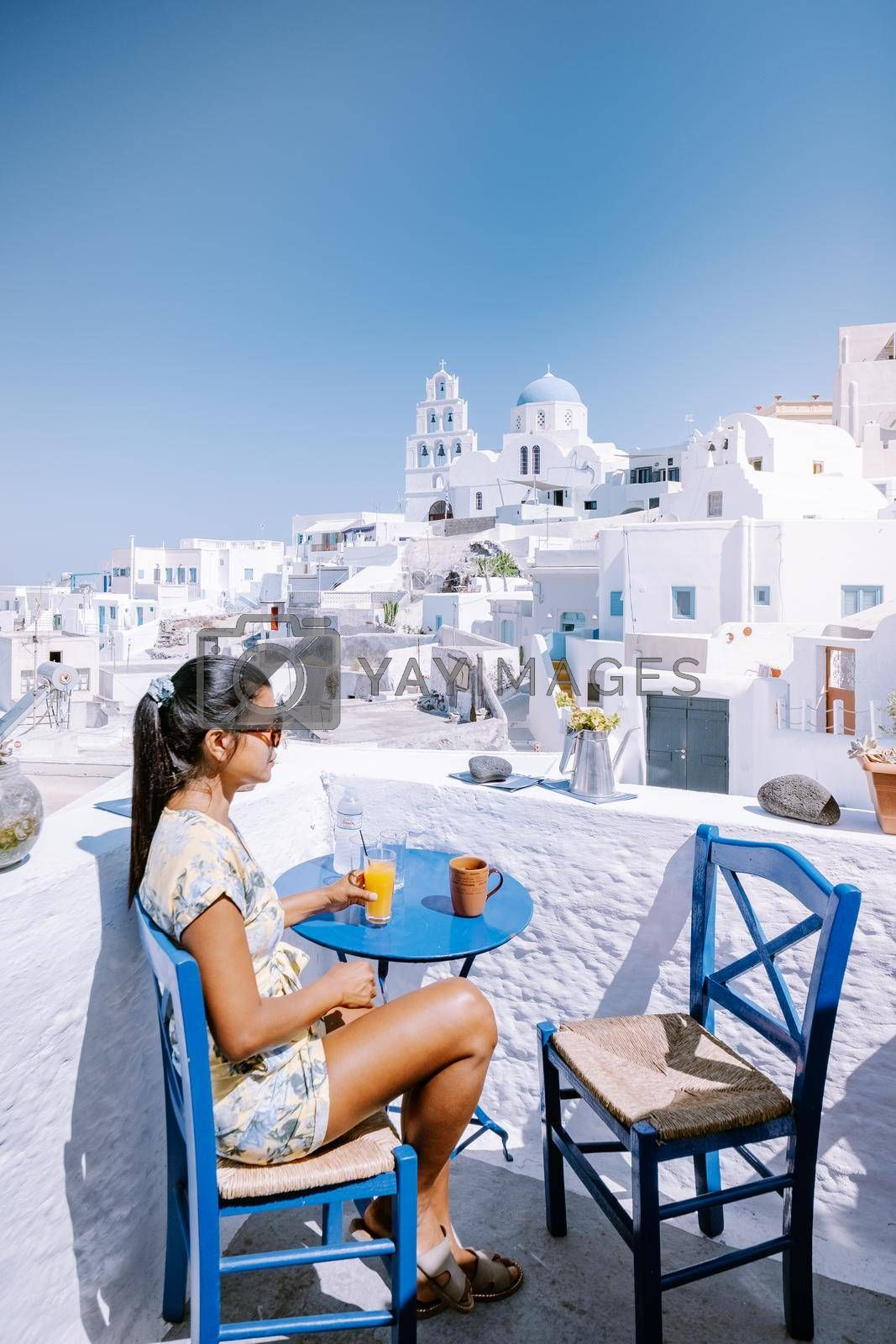 Royalty free image of Santorini Greece, young woman on luxury vacation at the Island of Santorini watching sunrise by the blue dome church and whitewashed village of Oia Santorini Greece during sunrise, men and woman on holiday in Greece by fokkebok