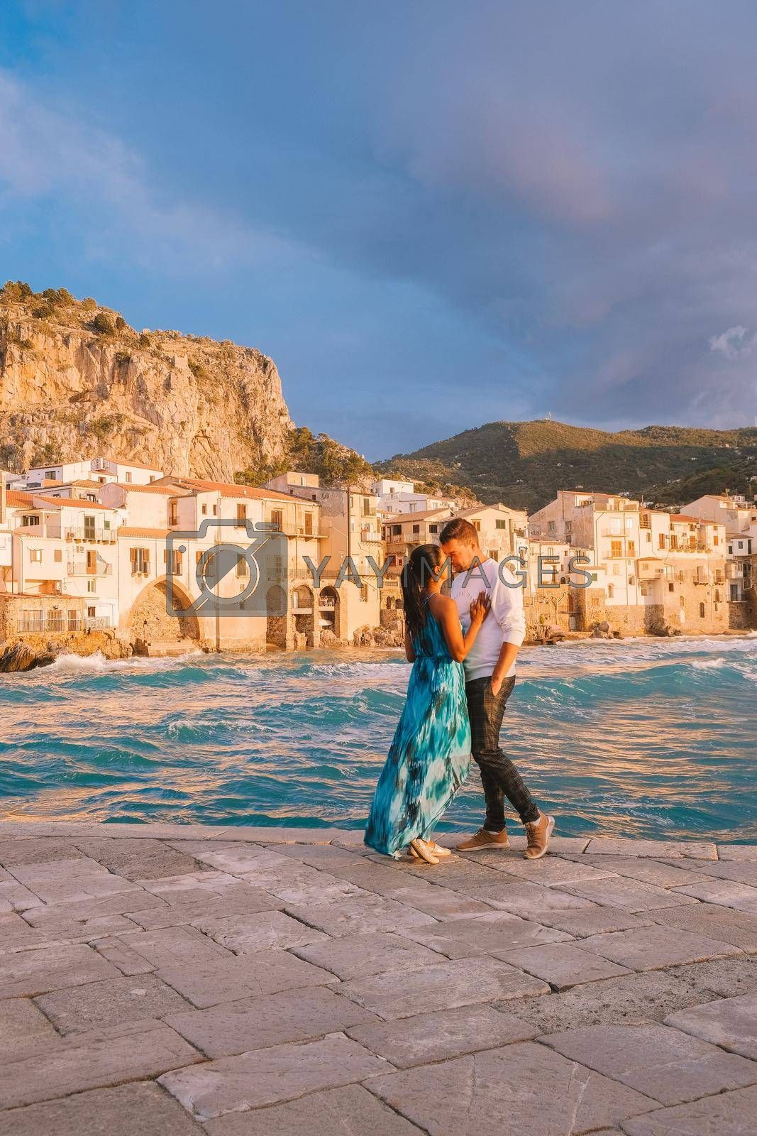 Royalty free image of Cefalu Sicily, couple watching sunset at the beach of Cefalu Sicilia Italy, mid age men and woman on vacation Sicily by fokkebok