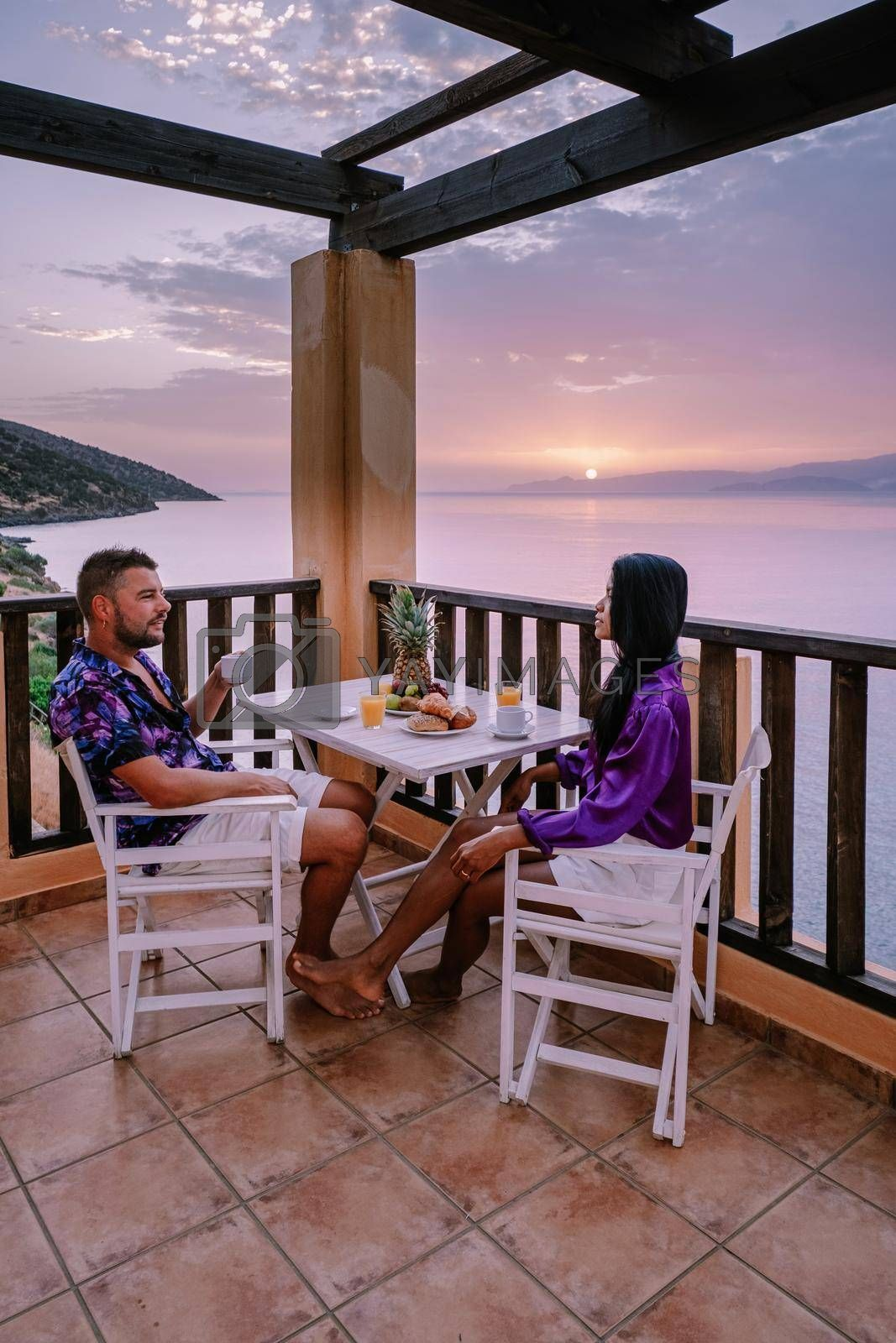 Royalty free image of table and chairs with breakfast during sunrise at the meditarian sea in Greece by fokkebok