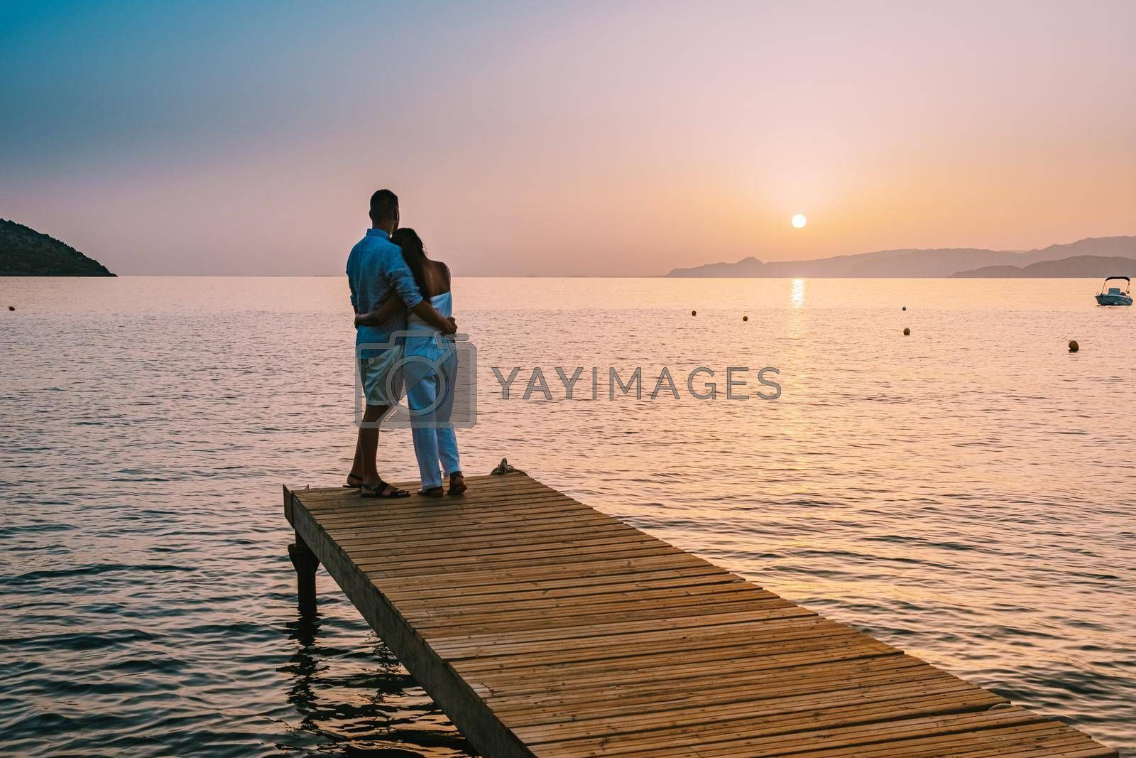 Royalty free image of Crete Greece, young romantic couple in love is sitting and hugging on wooden pier at the beach in sunrise time with golden sky. Vacation and travel concept. Romantic young couple dating at seaside by fokkebok