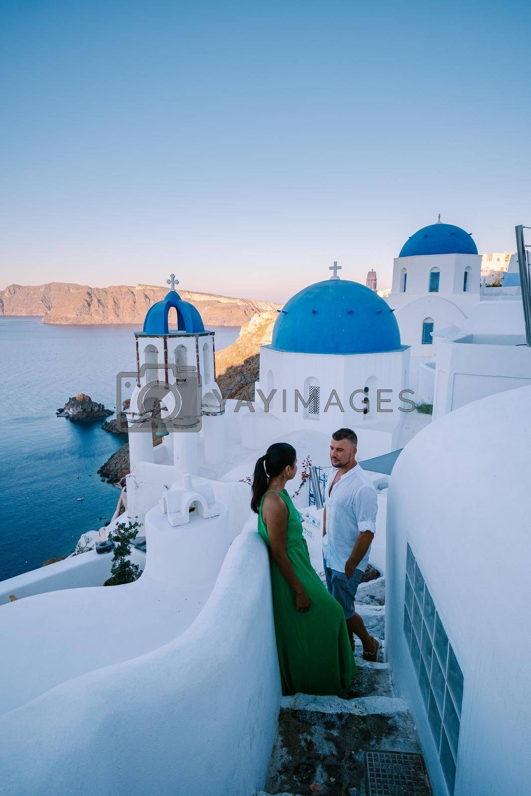 Royalty free image of Santorini Greece, young couple on luxury vacation at the Island of Santorini watching sunrise by the blue dome church and whitewashed village of Oia Santorini Greece during sunrise, men and woman on holiday in Greece by fokkebok