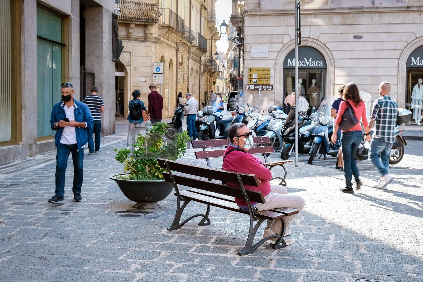 Royalty free image of Ortigia in Syracuse in the Morning. Travel Photography from Syracuse, Italy on the island of Sicily. Cathedral Plaza and market with people whear face protection during the 2020 pandemic by fokkebok