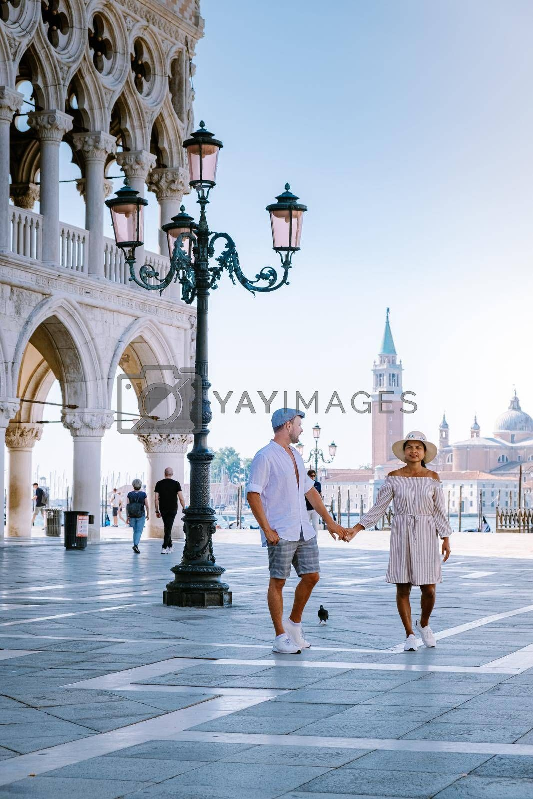 couple on a city trip in Venice, view of piazza San Marco, Doge's Palace Palazzo Ducale in Venice, Italy. Architecture and landmark of Venice. Sunrise cityscape of Venice Italy