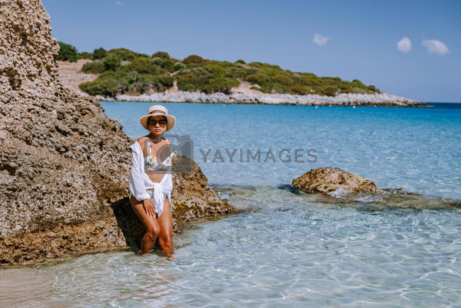 Tropical beach of Voulisma beach, Istron, Crete, Greece ,Most beautiful beaches of Crete island -Istron bay near Agios Nikolaos young asian woman mid age on vacation Greece Crete