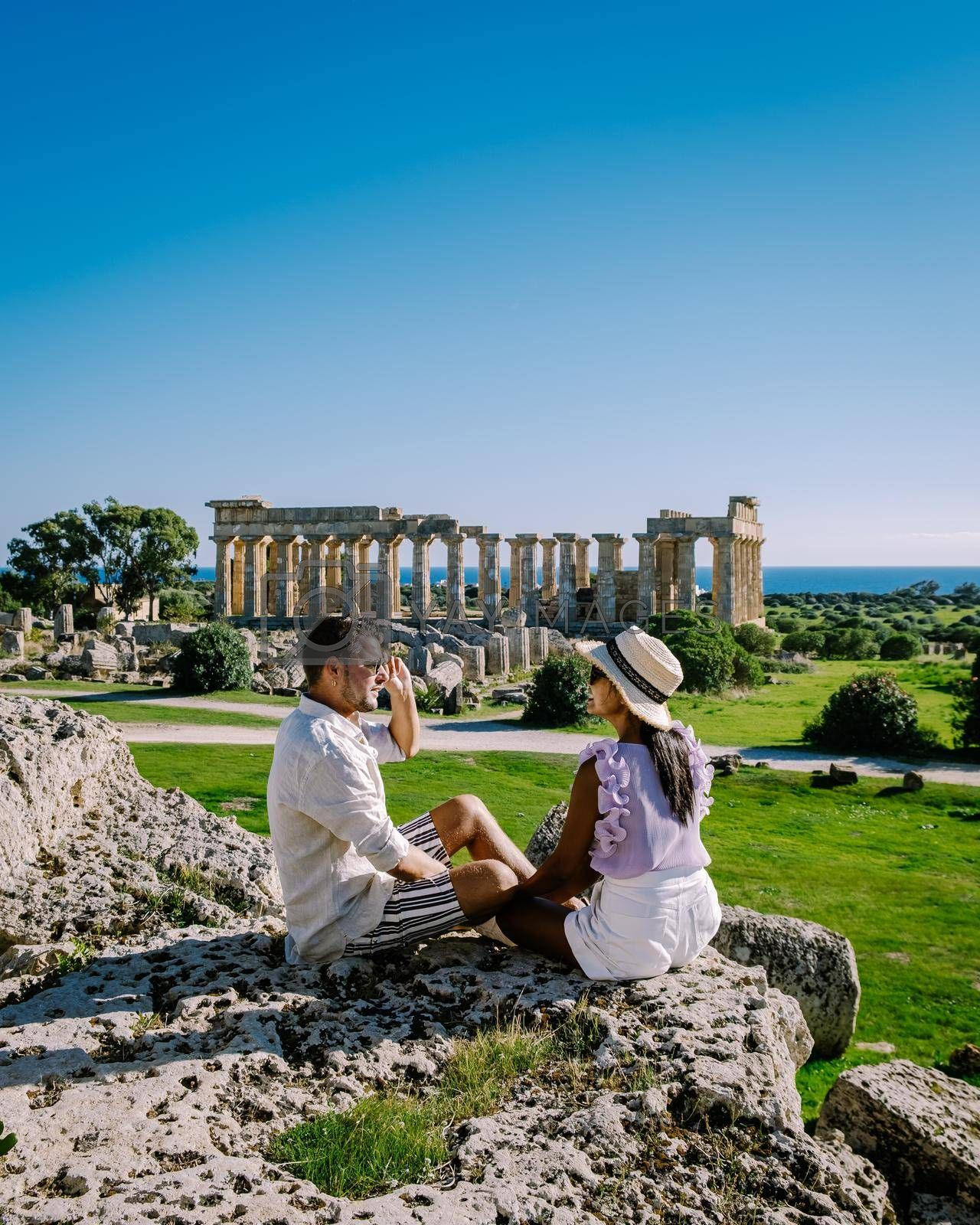 A couple visit Greek temples at Selinunte during vacation, View on sea and ruins of greek columns in Selinunte Archaeological Park Sicily Italy