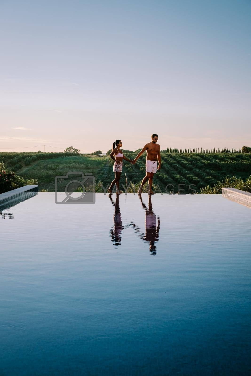Luxury resort with a view over the wine field in Selinunte Sicily Italy. infinity pool with a view over wine fields in Sicilia, a couple on luxury vacation at the Island of Sicily Italy