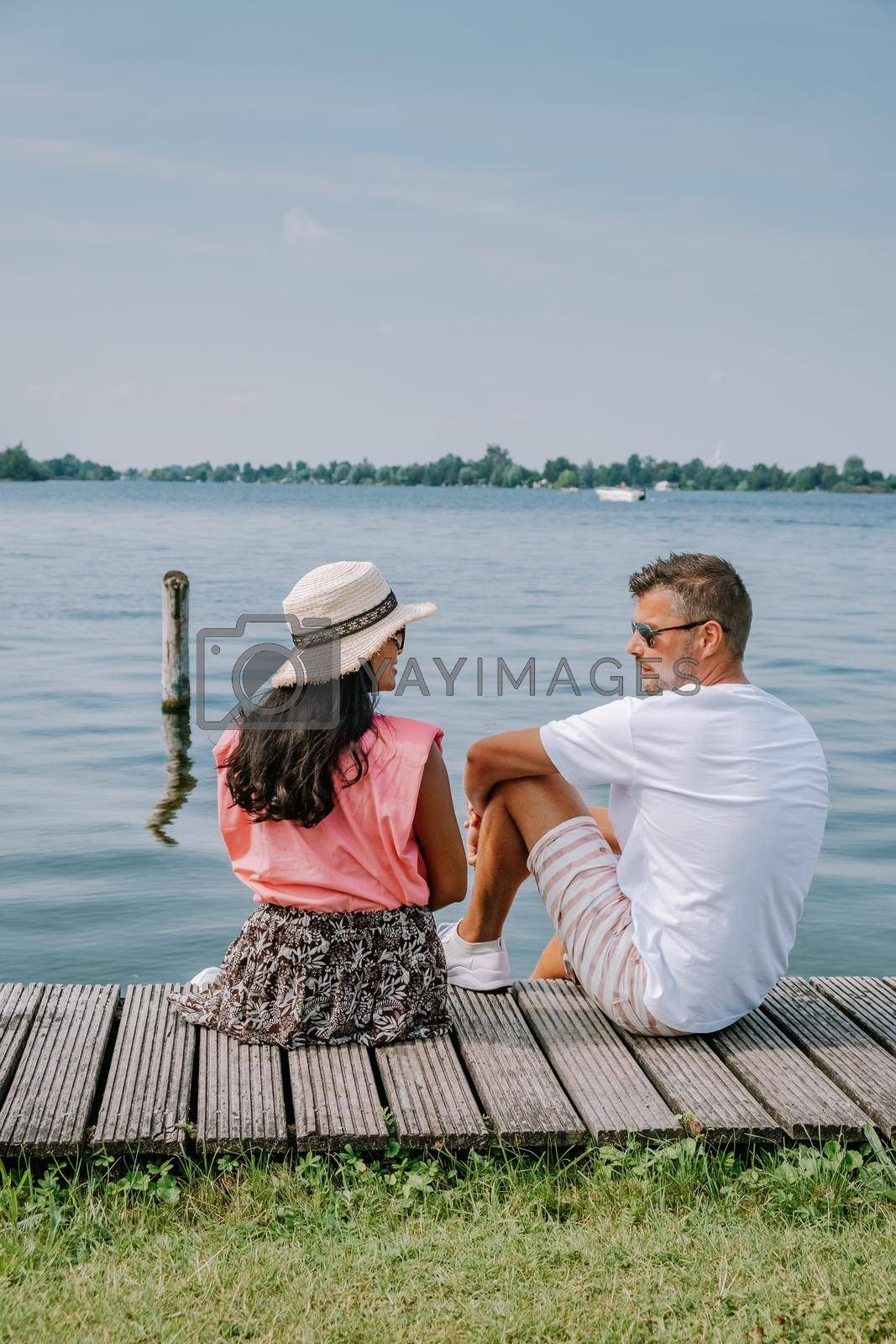 people relaxing in the park by the lake in the Netherlands Vinkeveen near Amsterdam, Vinkeveen is mainly famous for the Vinkeveense Plassen Lakes of Vinkeveen, an area of lakes and sand islands east of the village. It is an important recreational area Netherlands. Europe