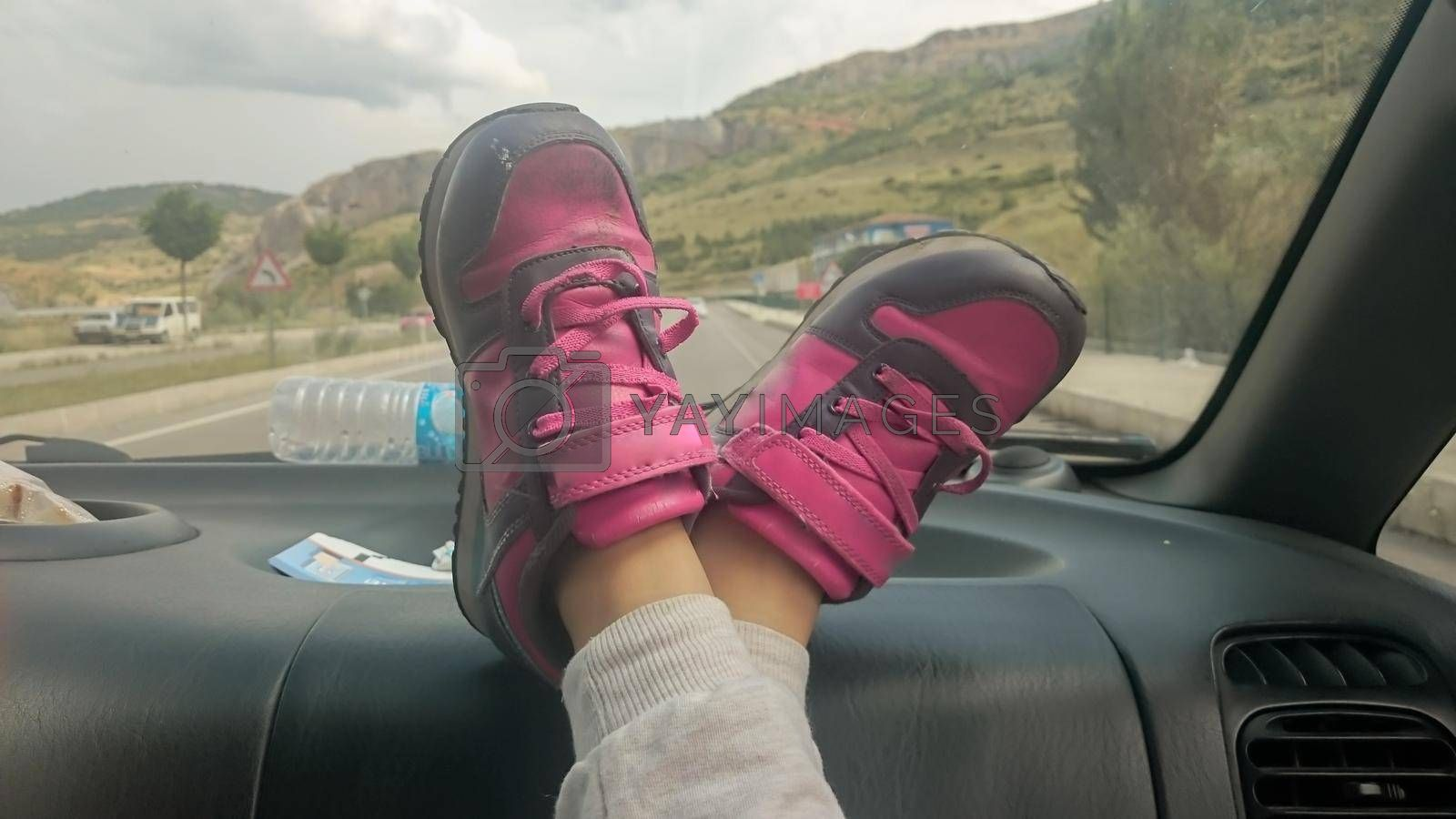 It depicts two pink shoes in a car in front of car window