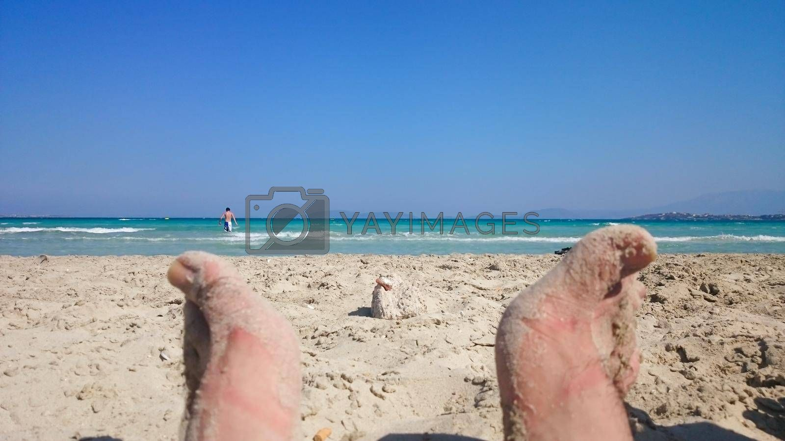 It depicts toes of a male person in a beach in a sunny day