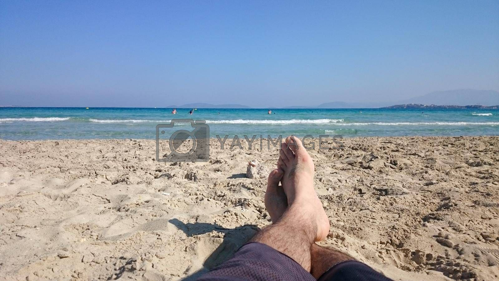 It depicts feet of a male person in a beach in a sunny day