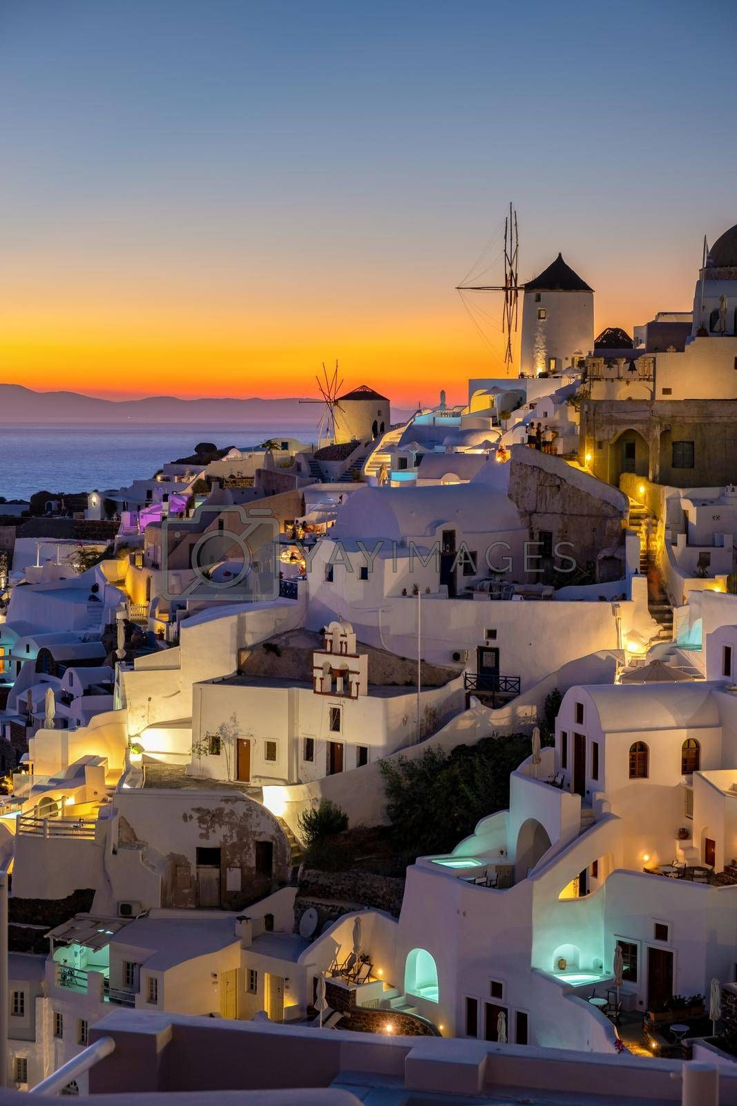 Sunset at the Island Of Santorini Greece, beautiful whitewashed village Oia with church and windmill during sunset, streets of Oia Santorini during summer vacation at the Greek Island
