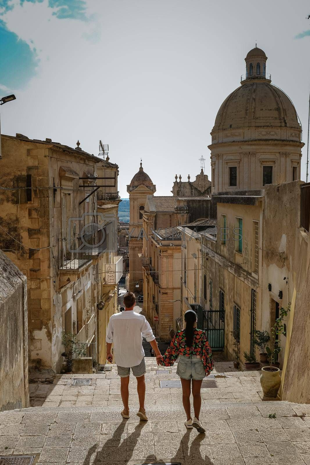 Sicily Italy, view of Noto old town and Noto Cathedral, Sicily, Italy. beautiful and typical streets and stairs in the baroque town of Noto in the province of Syracuse in Sicily, a couple on city trip Noto
