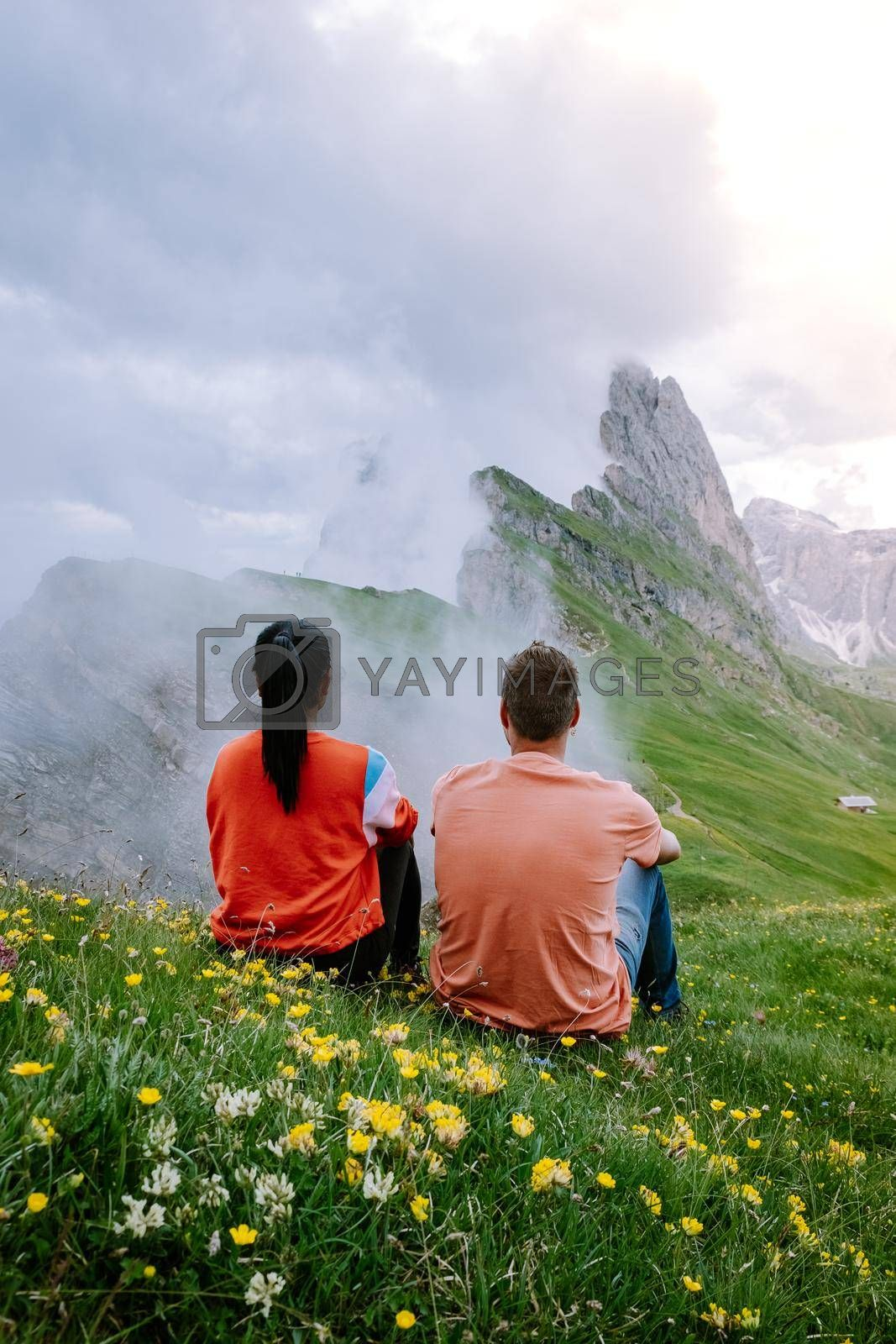 couple on vacation hiking in the Italien Dolomites, Amazing view on Seceda peak. Trentino Alto Adige, Dolomites Alps, South Tyrol, Italy, Europe. Odle mountain range, Val Gardena. Majestic Furchetta peak in morning sunlight. Italy