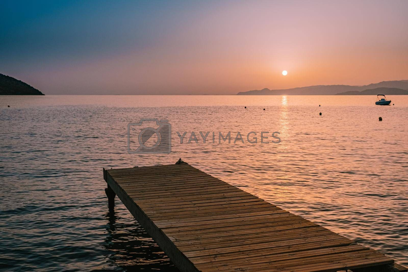 wooden pier at the beach in sunrise time with golden sky. Vacation and travel concept. Crete Greece