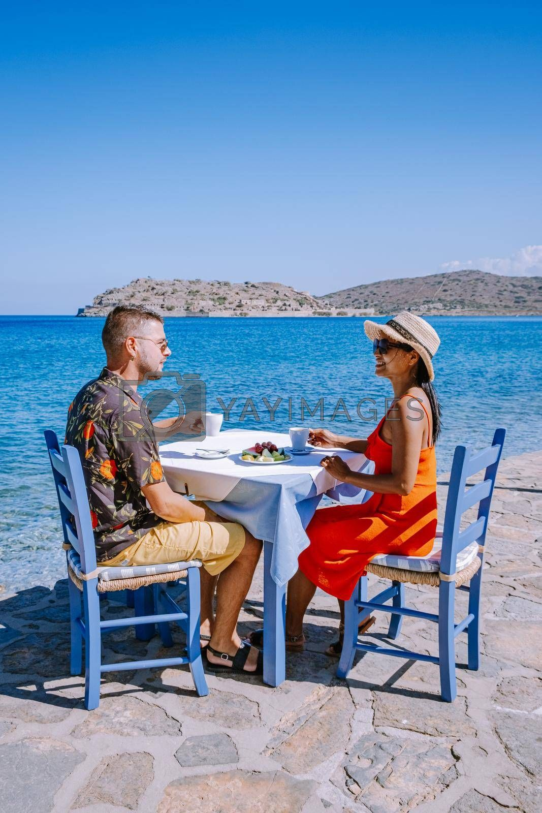 Crete Greece Plaka Lassithi with is traditional blue table and chairs and the beach in Crete Greece. Paralia Plakas, Plaka village Crete, couple on vacation holiday in Greece