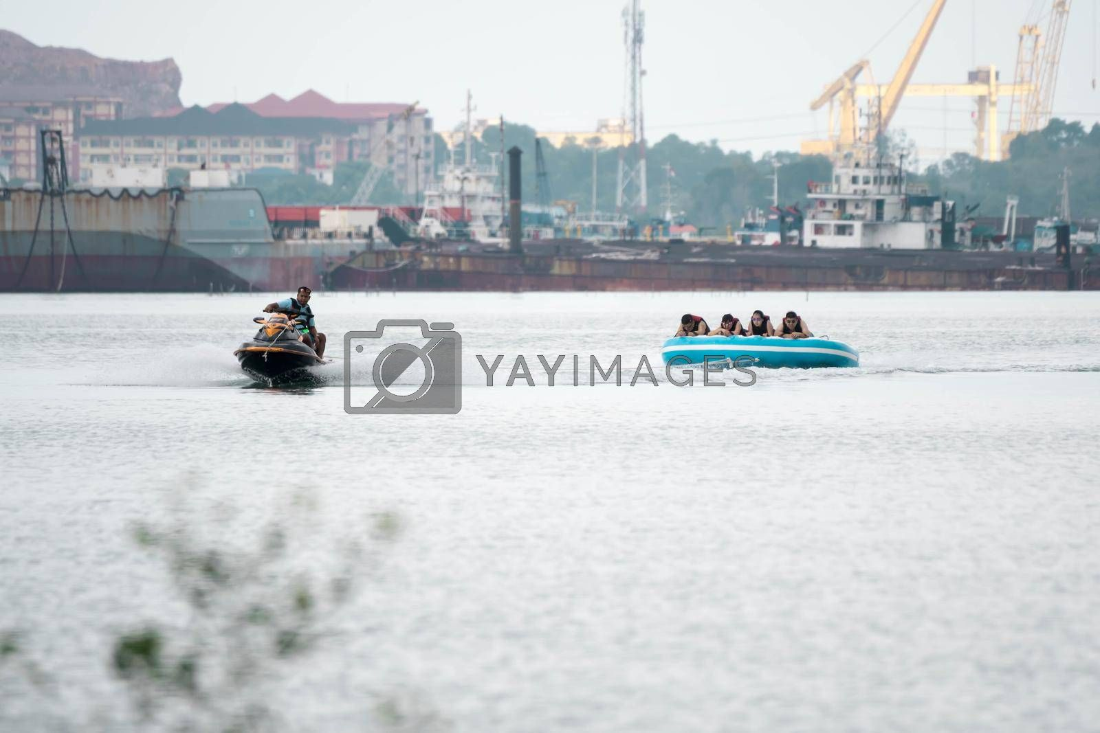 Beach water sports tubing with tourist being pulled by jetski in a beach in batam indonesia, Indonesia, May 4 2019