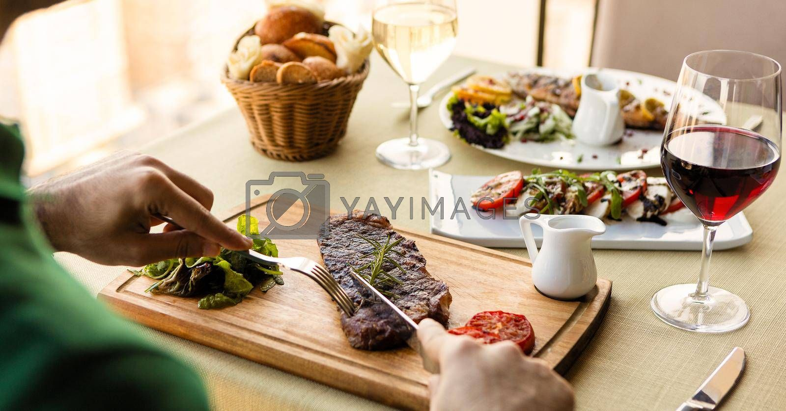 Man cutting tasty steak with sauce, salad on the table