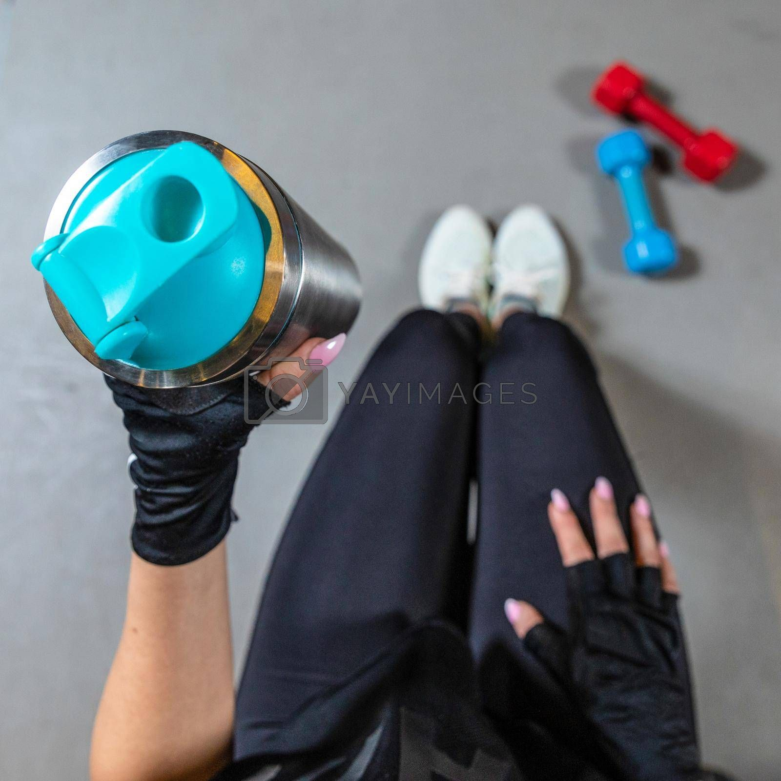 Cropped photo of fitness woman sitting in gym and holding bottle of water