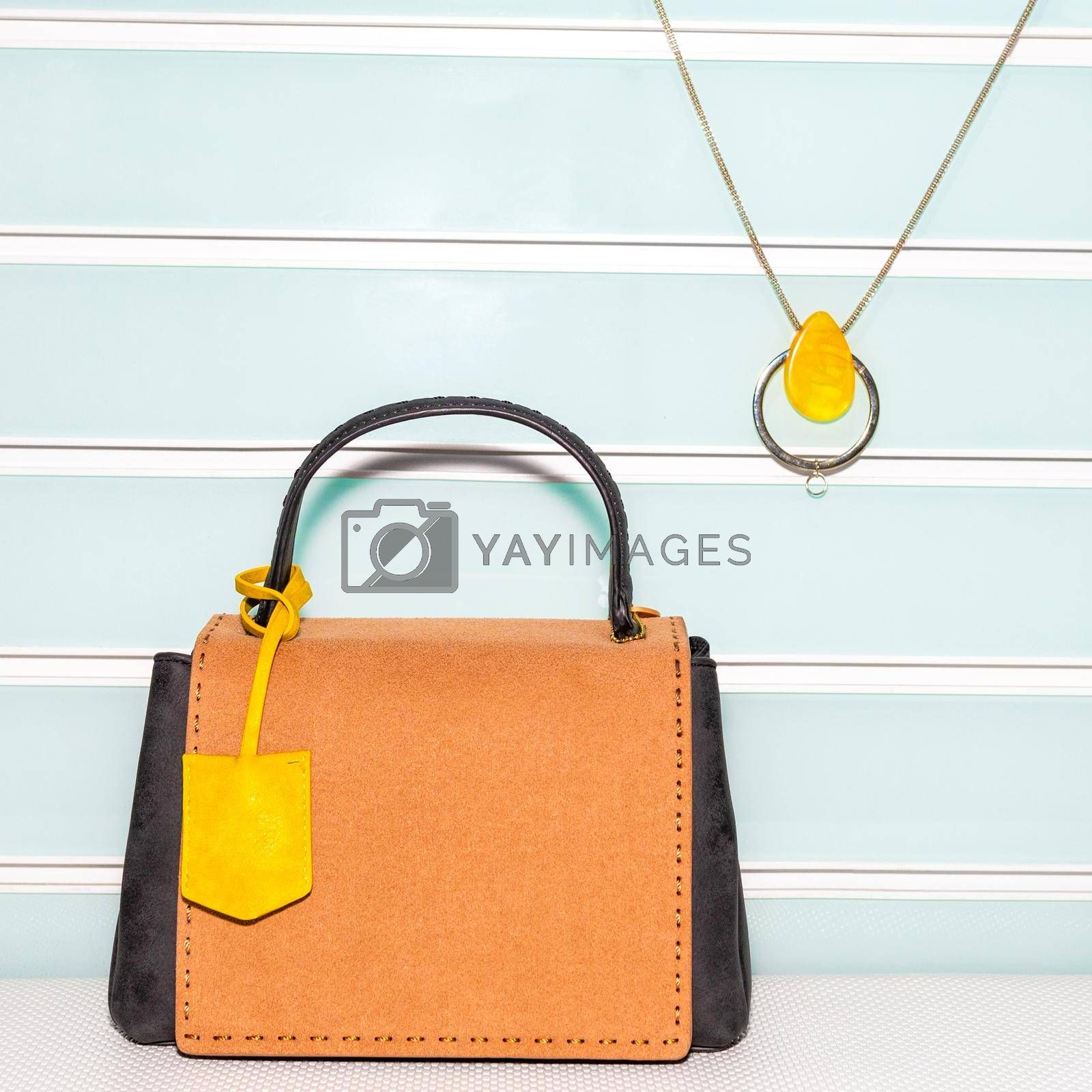 Yellow female bag with accessorize on a white background isolated