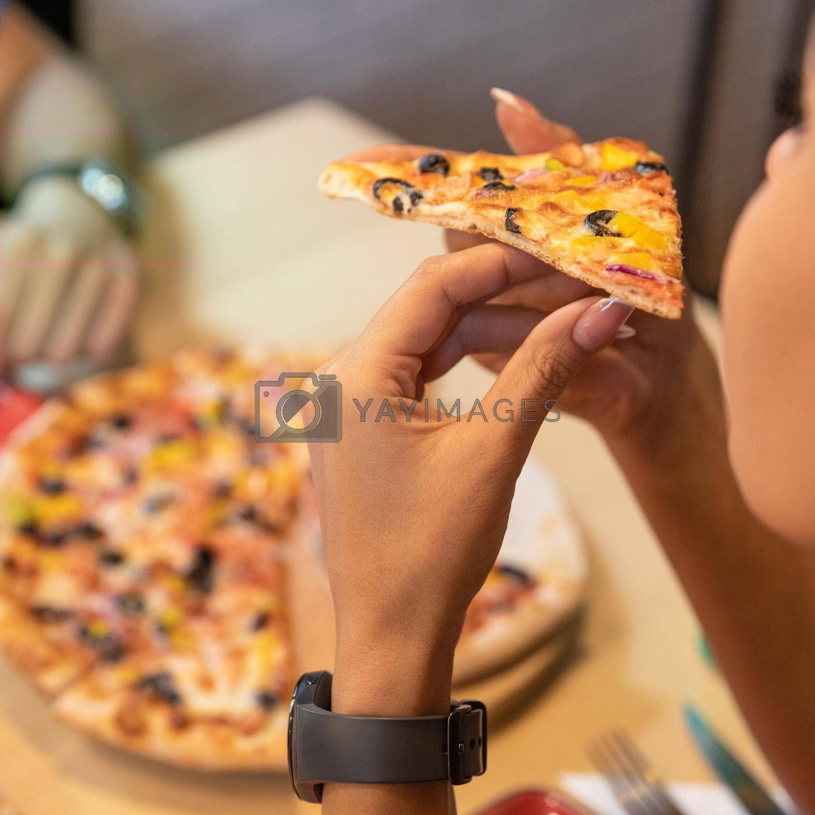 Woman eating tasty pizza, close up