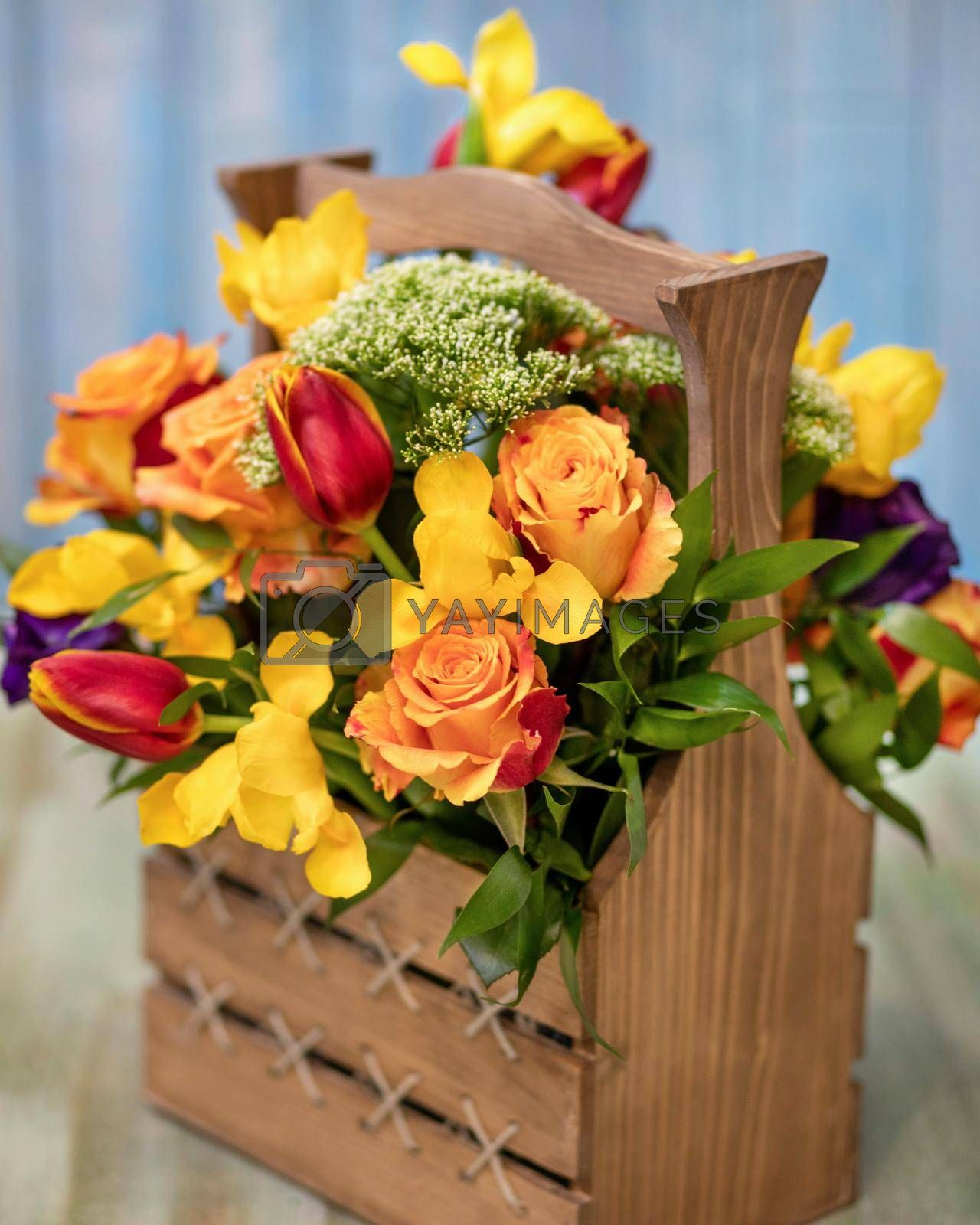Colorful flower bouquet in the wood box with blue background