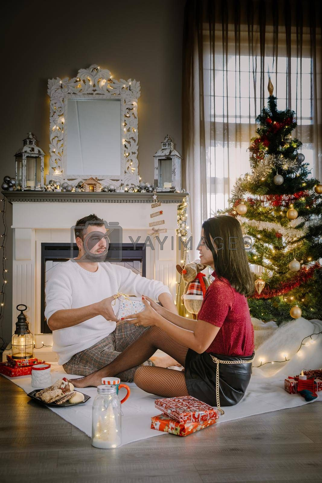 Royalty free image of Family sitting on a floor. Couple near christmas tree, Christmas couple with present by fokkebok