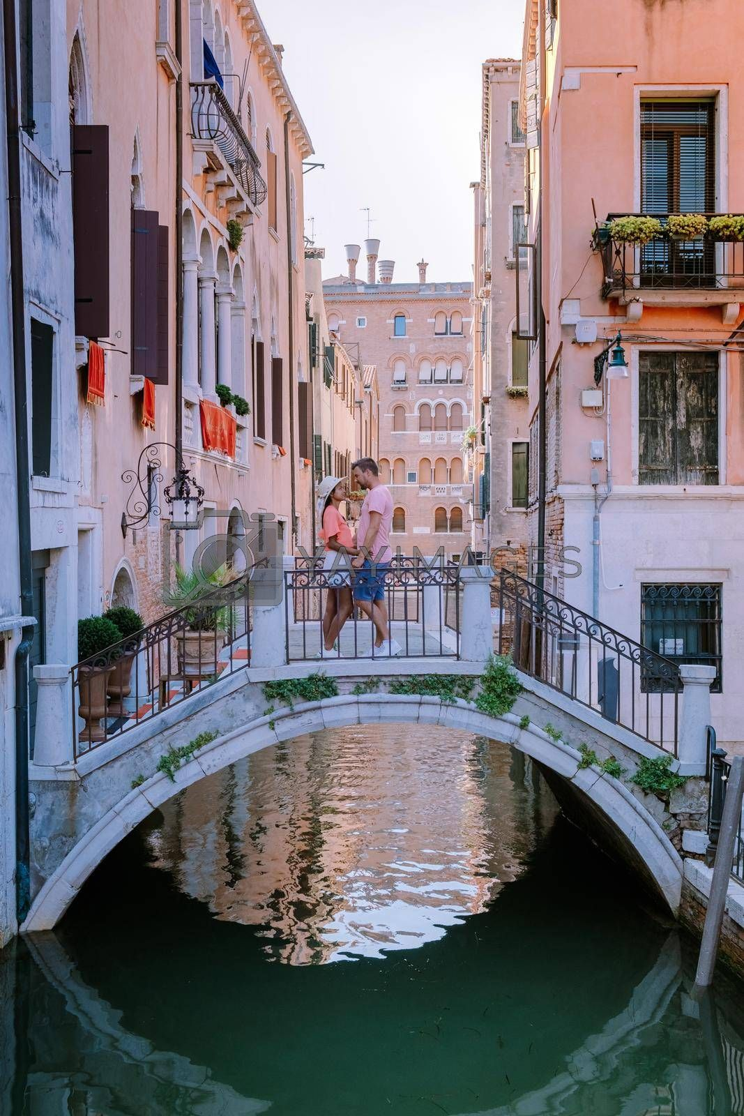couple men and woman on a city trip to Venice Italy, colorful streets with canals Venice. Europe