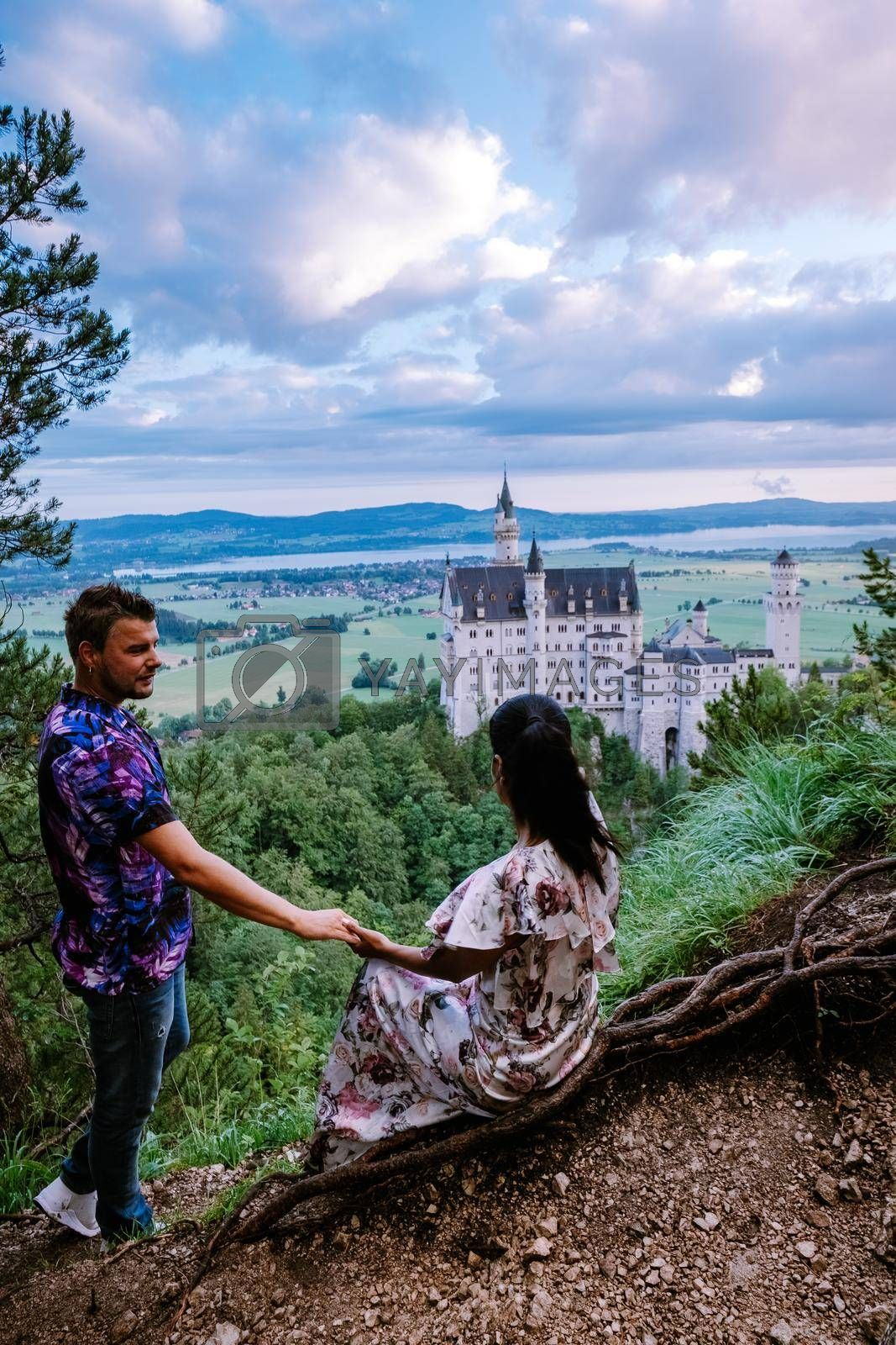 couple men and woman visit Neuschwanstein Castle, Beautiful view of world-famous Neuschwanstein Castle, the nineteenth-century Romanesque Revival palace built for King Ludwig II on a rugged cliff near Fussen, southwest Bavaria, Germany. Europe