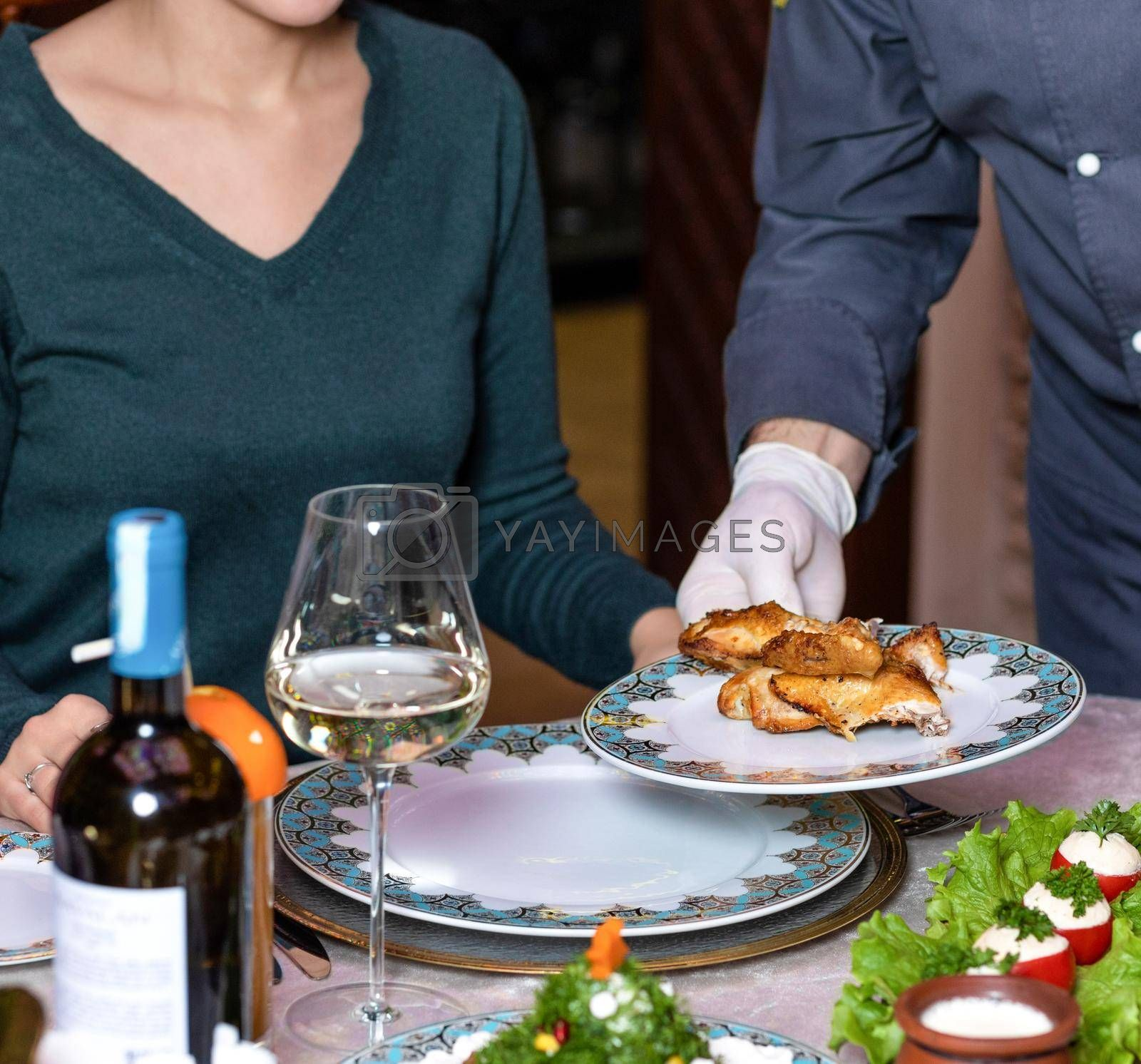 Waiter serving a chicken meat to the woman