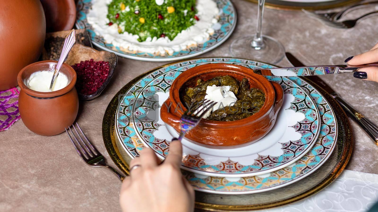 Woman eating Dolma, Azerbaijani meal top view
