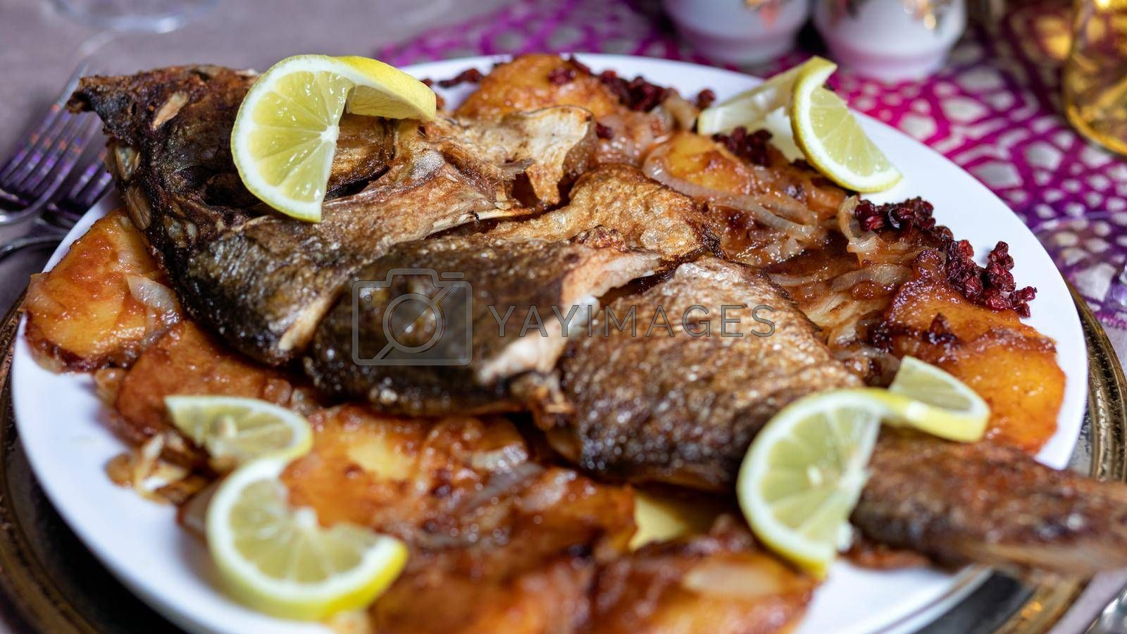 Grilled whole fish with a lemon close up