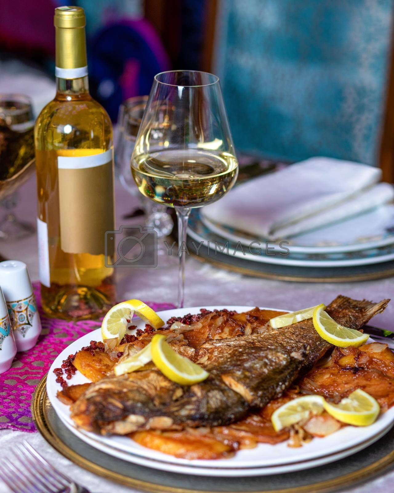 Grilled whole fish with a lemon and white wine close up