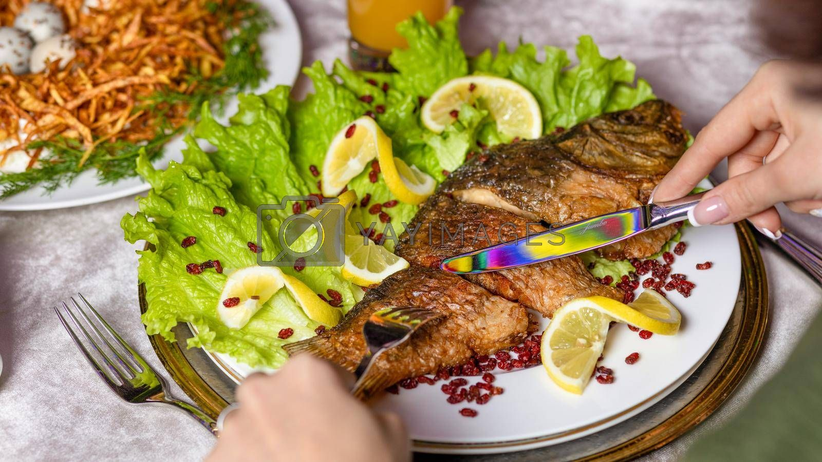Woman eating a grilled whole fish with a lemon