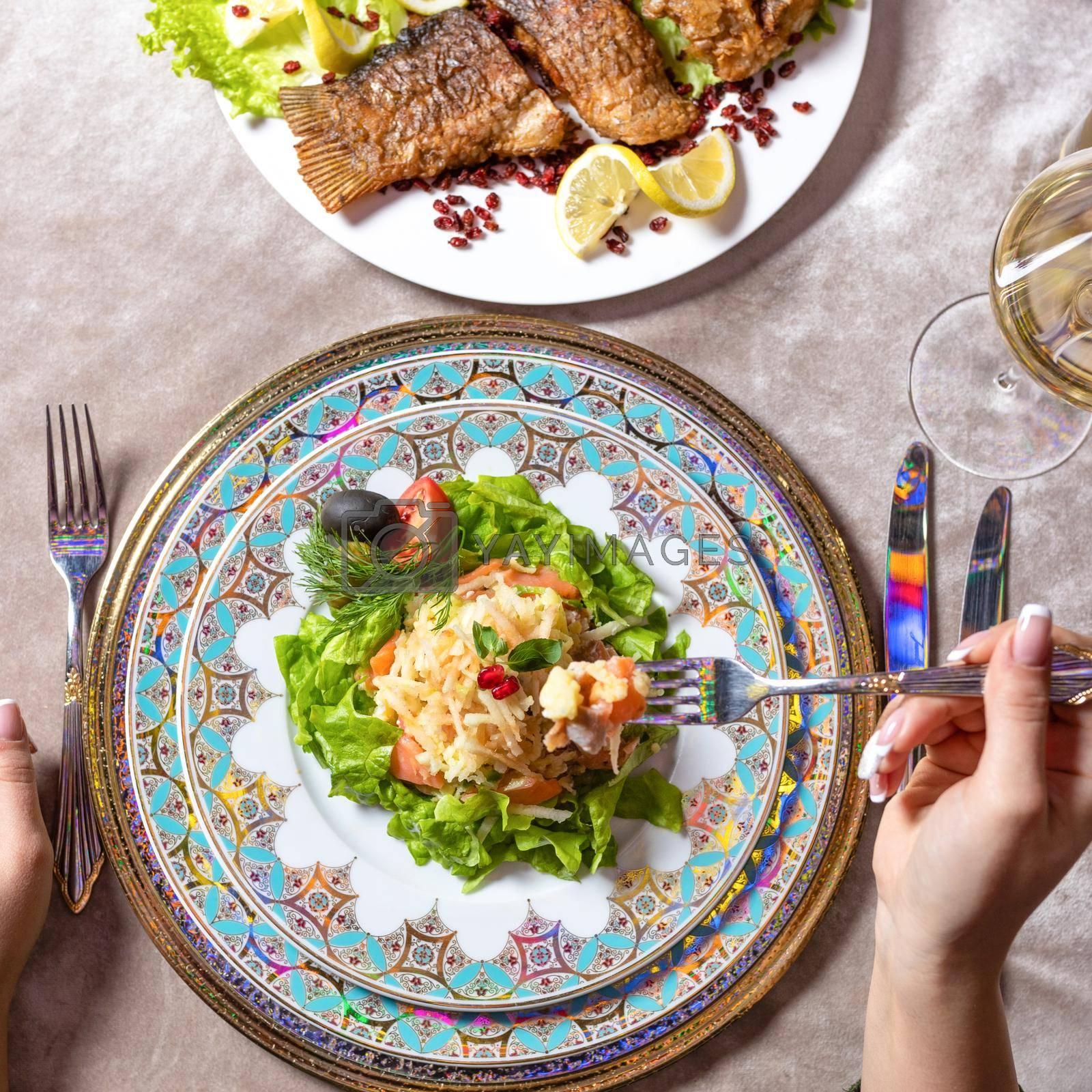 Woman eating a fish salad top view