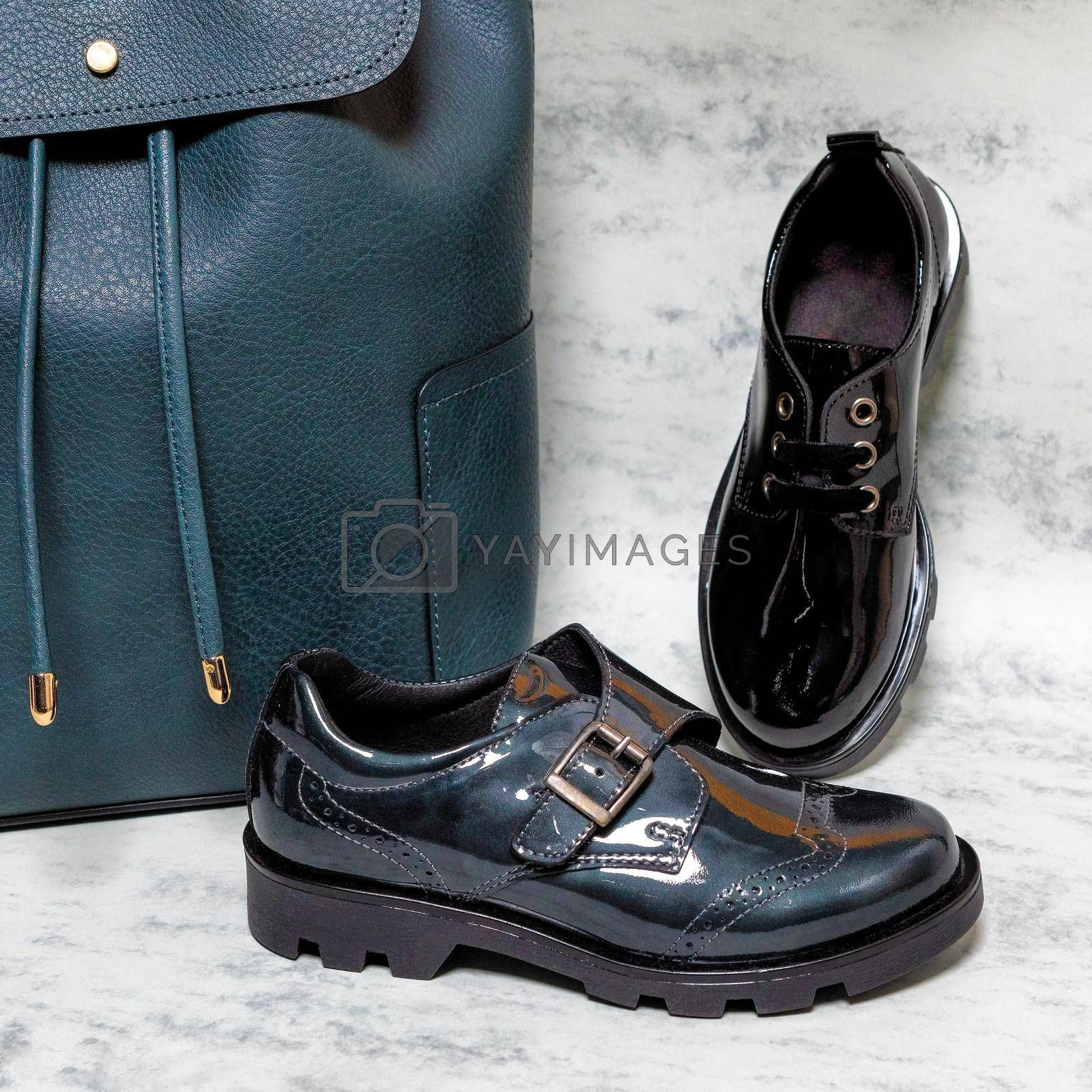 Black shiny boy male shoes with a blue backpack isolated