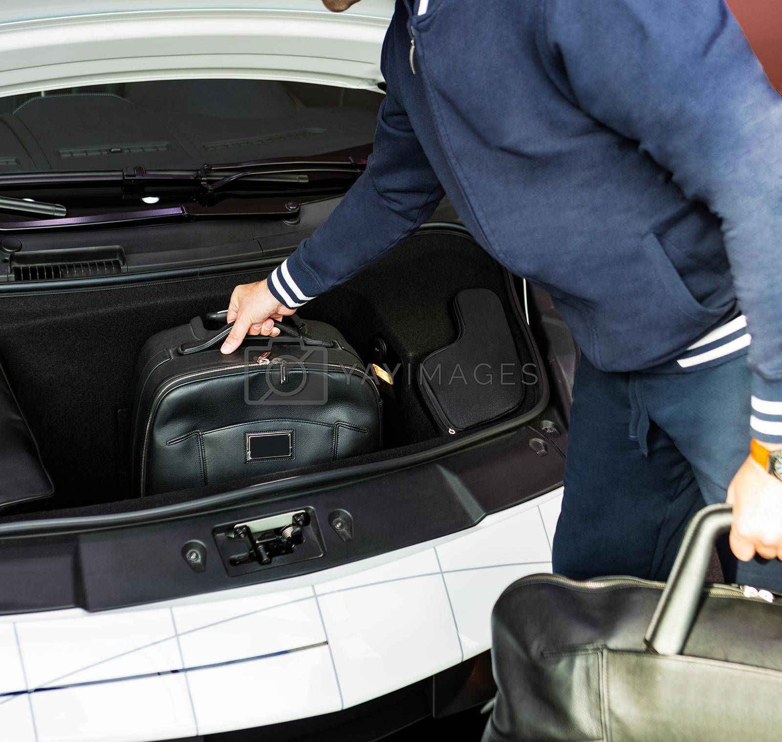 Man putting bag, baggage to the sports car front luggage