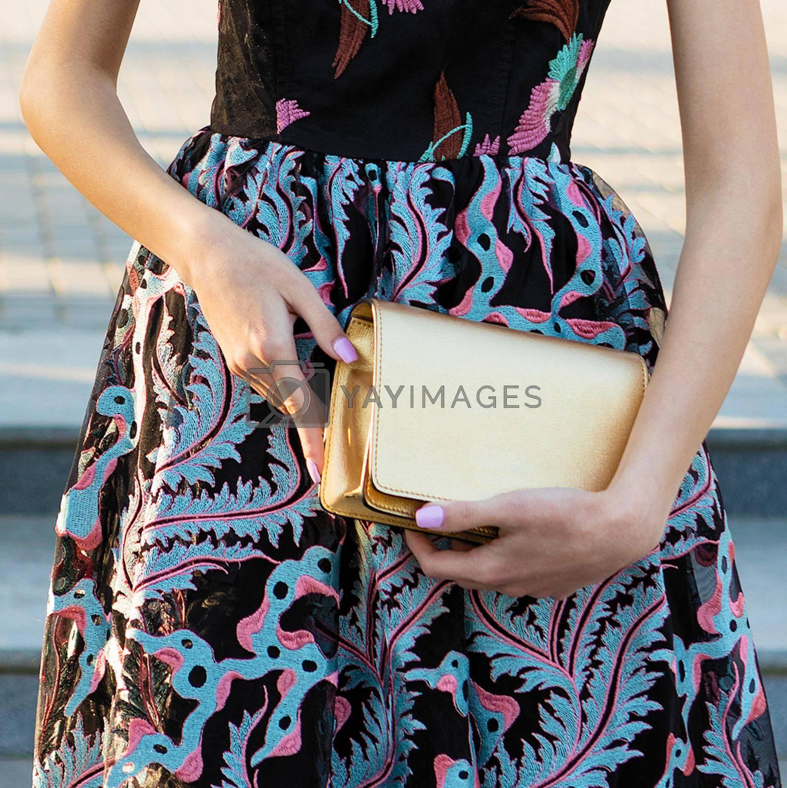 Woman holding a golden handbag close up