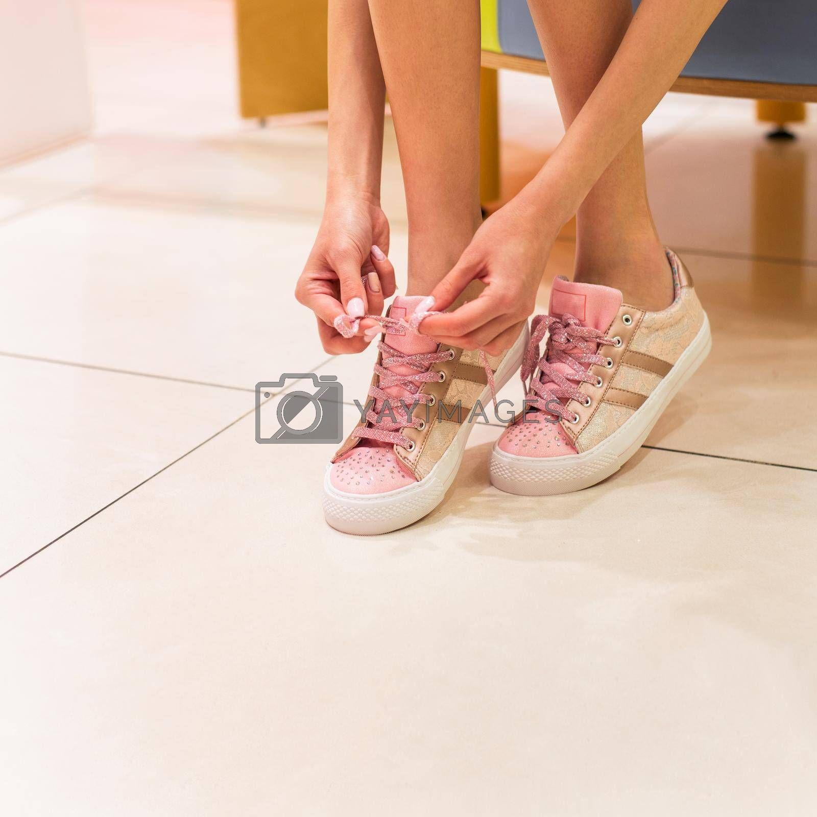 Woman tying her shoes. Pink shiny color girl shoes isolated