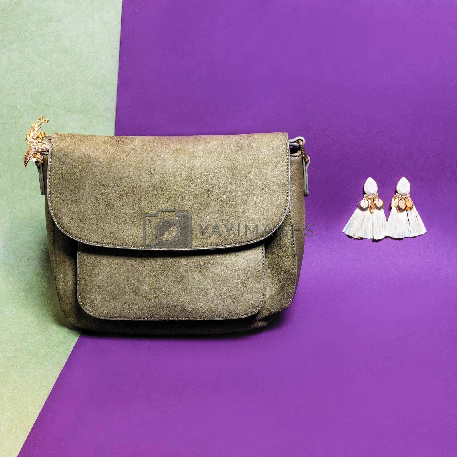 Leather color woman handbag with earrings isolated